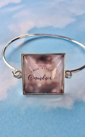 """Love Conquers All"" slogan bangle bracelet in silver and pink by Soul Warriors"