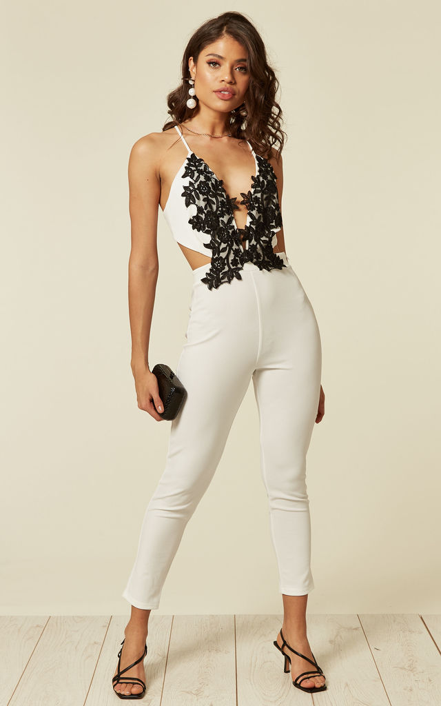 White Lace Plunge Neck Jumpsuit With Crossed Back And Front Floral Applique by Off The Railz
