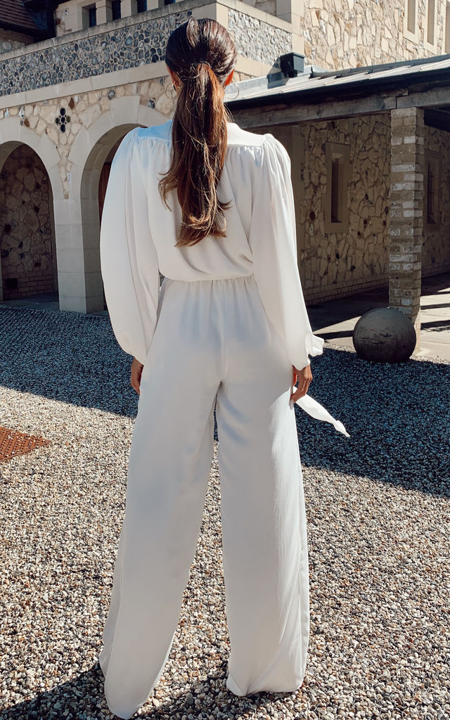 White satin wrap jumpsuit with oversized bell sleeves and tie waist by SHE BY SOPHIE